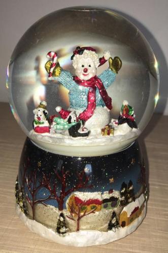 Draaiende sneeuwpop in glazen bol met kerst muziek