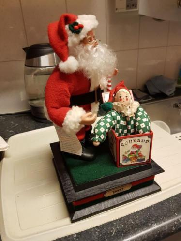 Leuke Kerstman met kerstcadeau met pop